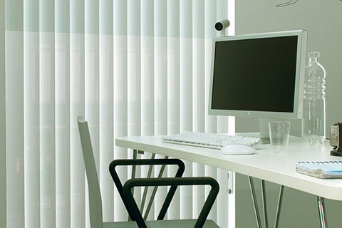 Photo of small office with vertical hanging blinds