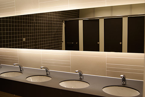 A photo of a new modern office male washroom in browns. Washroom and Toilet Facilities from Complete Interiors