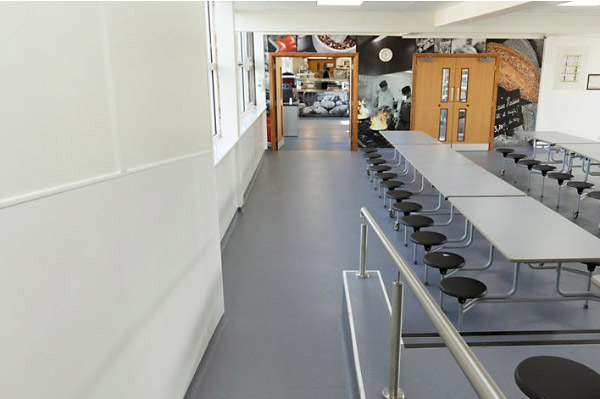 A photo looking down a refurbished student dining hall from the entrance way